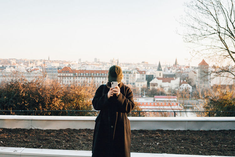 Woman standing by tree in city against sky during winter