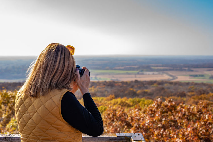 Side view of woman photographing landscape with camera