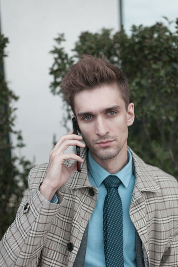Portrait of businessman talking on mobile phone in city