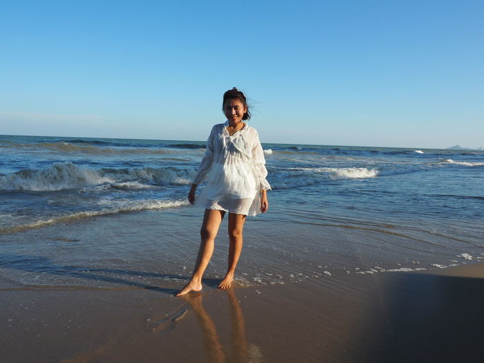 Full length of woman standing on beach against clear sky