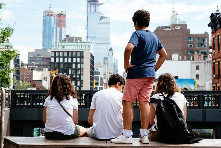 Family looking at the cityscape of New York from High Line Chelsea City Cityscape Family High Line Park Travel Adult Architecture Building Building Exterior Built Structure Casual Clothing City City Life Cityscape Day Group Of People Hairstyle Journey Leisure Activity Lifestyles Looking At View Men Nature Office Building Exterior Outdoors People Real People Rear View Sitting Skyscraper Togetherness Women