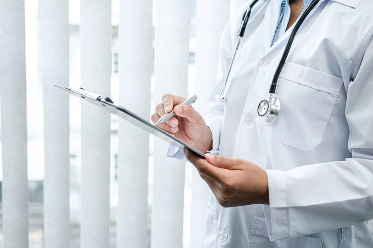 Midsection of doctor writing in clipboard at hospital