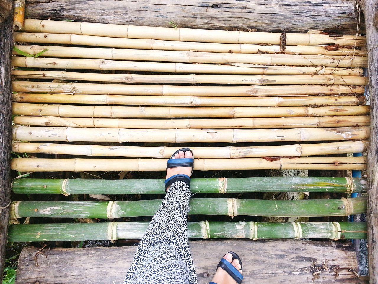 Low Section Of Woman Walking On Bamboo Walkway