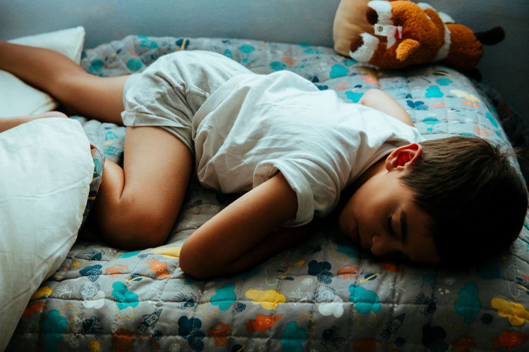 High Angle View Of Cute Boy Sleeping On Bed At Home