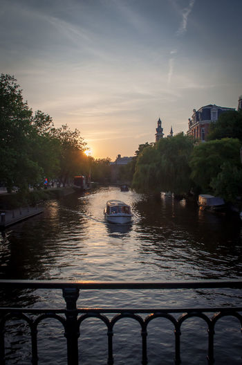 Boats in river against sky at sunset