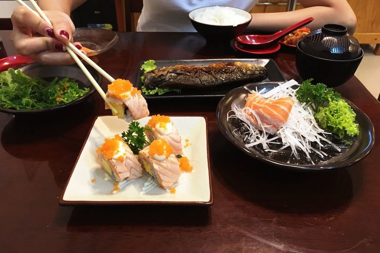 Cropped hand holding sushi with chopsticks on table