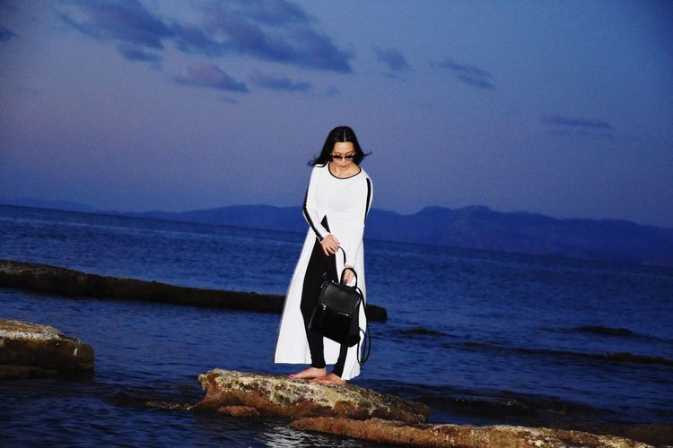 Full length of woman standing on rock at beach against sky holding a bag