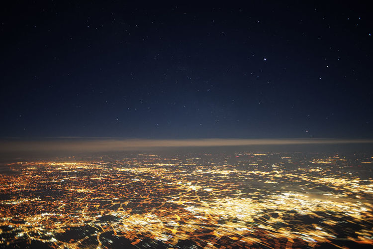 Aerial view of illuminated city against sky at night