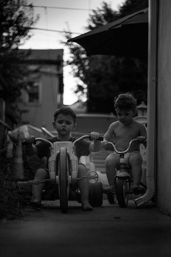 Full Length Of Siblings Riding Tricycle On Walkway