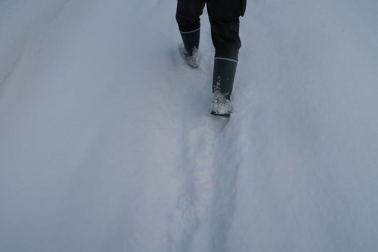 Low section of person walking on snow covered land