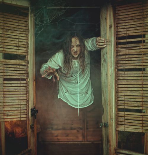 Portrait of woman dressed as zombie standing at window