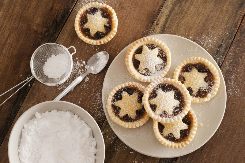 High angle view of star shape mince pie in plate on wooden table