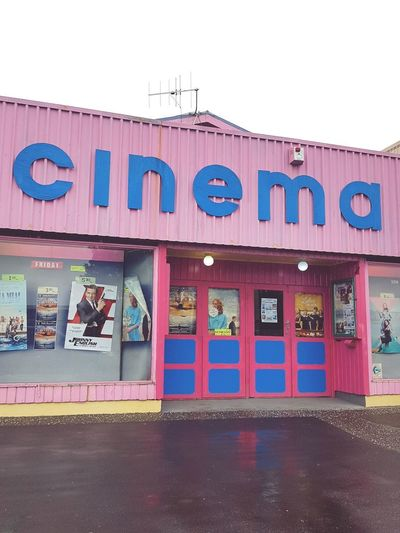 pink and blue regional cinema in Whangamatta, New Zealand MOVIE Pink Building Pink Regional Regional Cinema Cinema Regional New Zealand City Awning Business Finance And Industry Text Built Structure Sky Commercial Sign