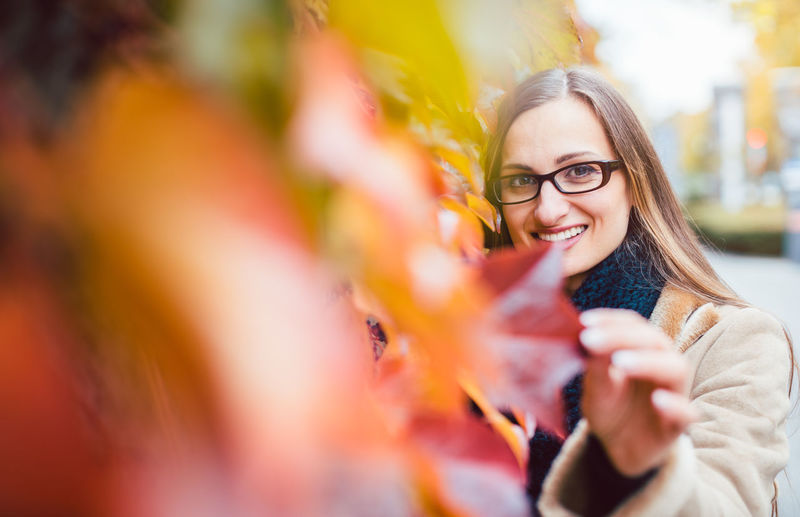 Portrait of smiling woman standing by plant
