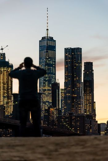 Rear view of man against brooklyn bridge and one world trade center in city