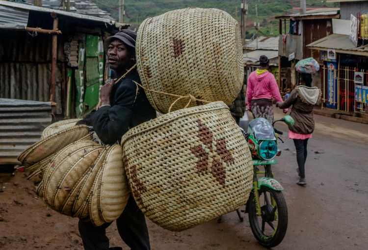 Portrait of man carrying containers on road in city