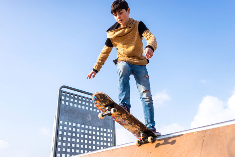 Low angle view of young man against blue sky