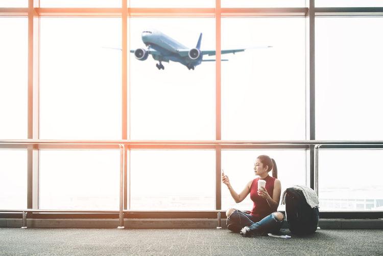 Full length of woman sitting on airplane window