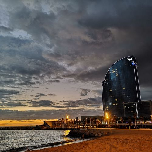 View of illuminated buildings at beach against cloudy sky