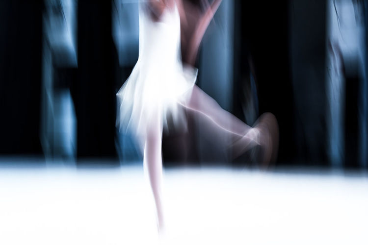 Blurred motion of female dancer dancing in room
