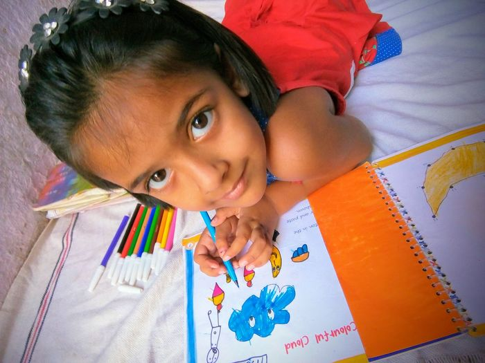 Close-Up Of Girl Coloring On Book At Home
