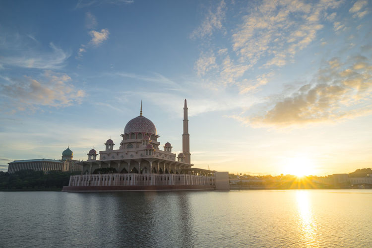 Mosque by river against sky during sunrise