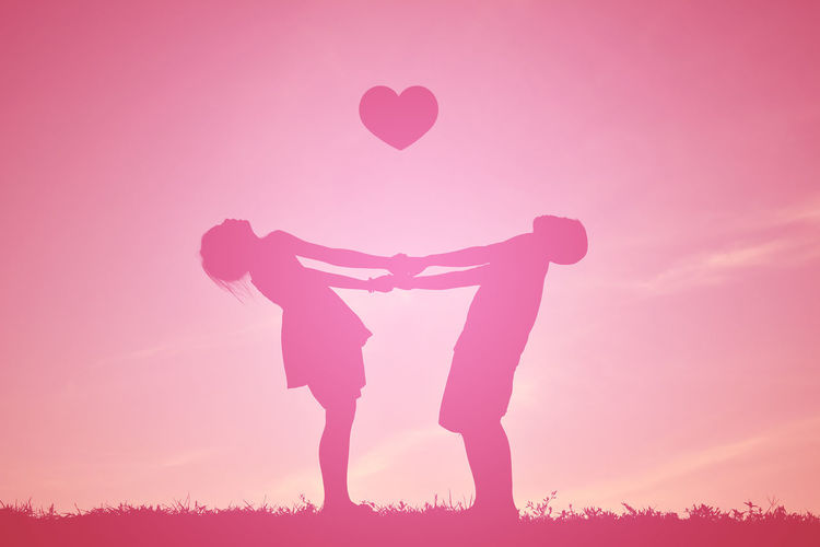 Boy and girl holding hands while standing below heart shape against sky during sunset