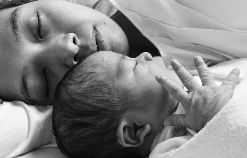 Close-up of mother and cute daughter sleeping on bed at home