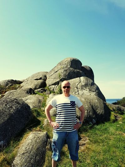 Man standing by rock against sky