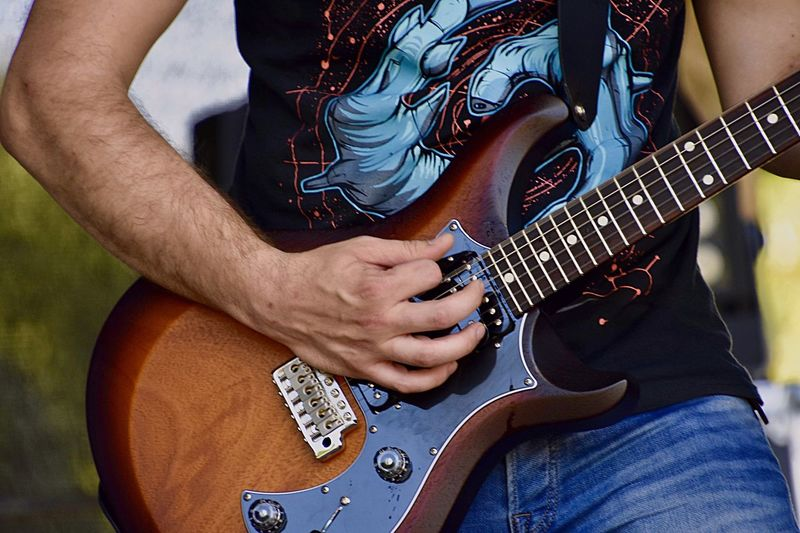 Midsection of man playing guitar outdoor