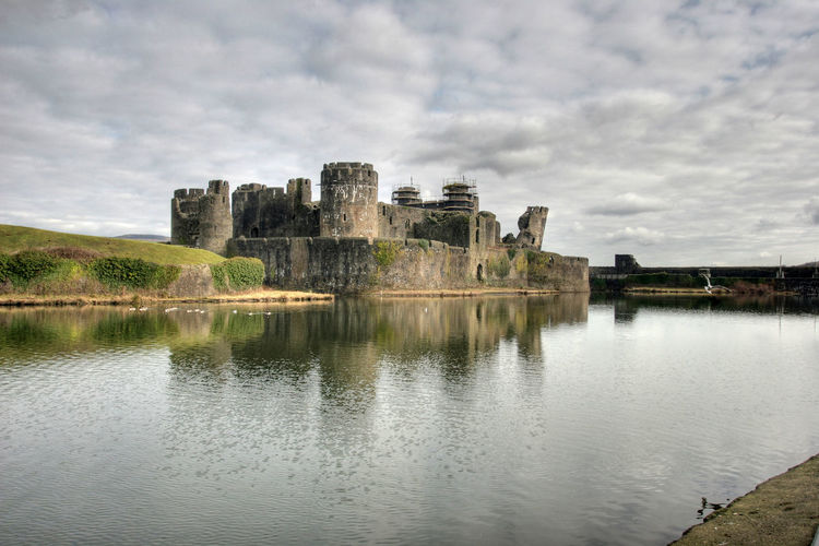 Caerphilly castle by lake against cloudy sky