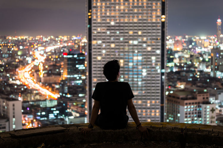 Rear view of mid adult man looking at illuminated cityscape while sitting on building terrace during night