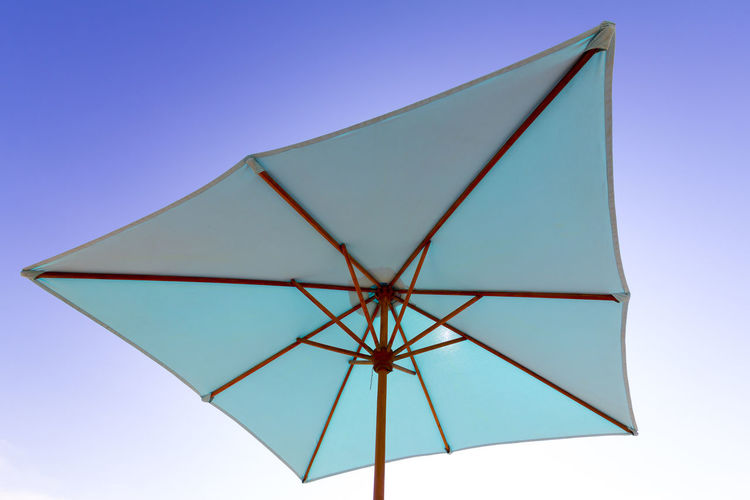 Low angle view of umbrella against clear blue sky