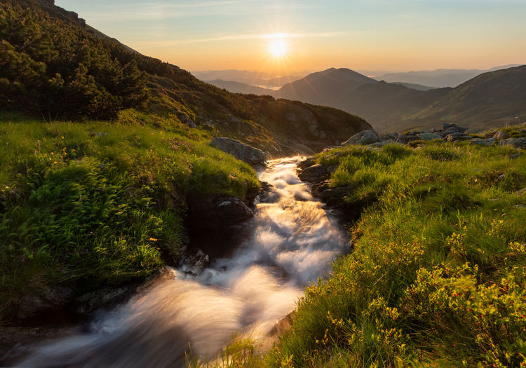 Scenic view of waterfall against sky during sunset