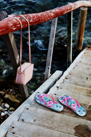 High angle view of flip-flops on wooden bridge by bag hanging on railing