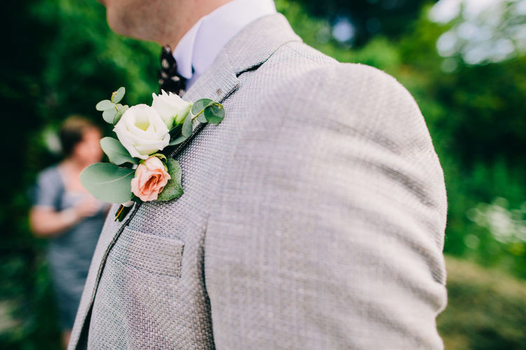 Midsection of bridegroom with flower on suit standing outdoors