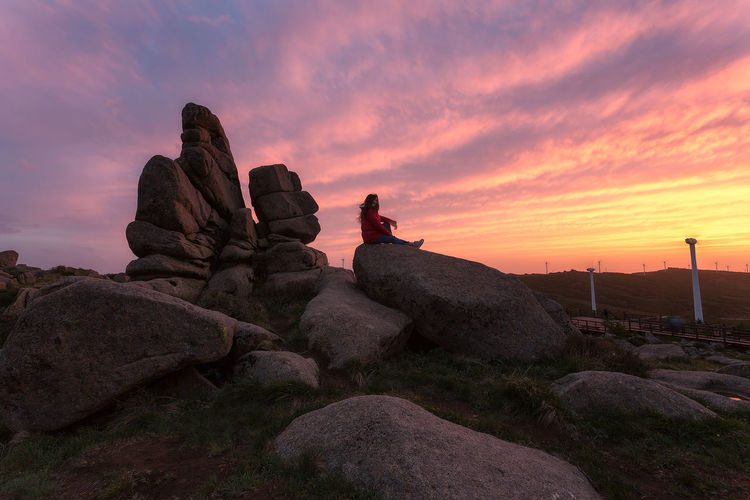 Man looking at rocks against sky during sunset