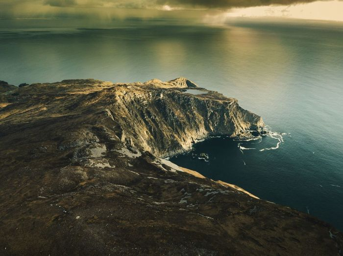 Aerial view of rock mountain by sea