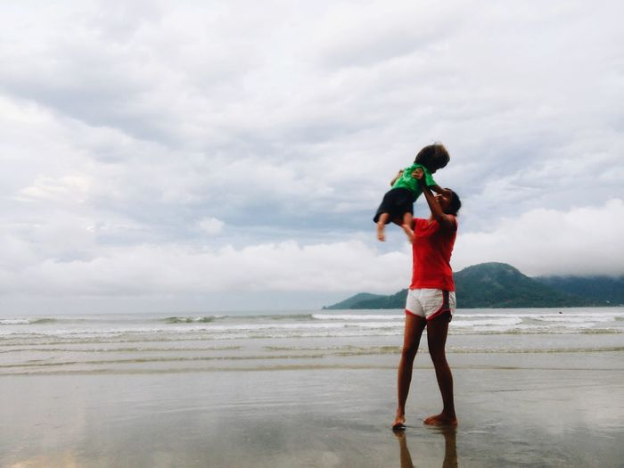 Mother holding son at beach against cloudy sky