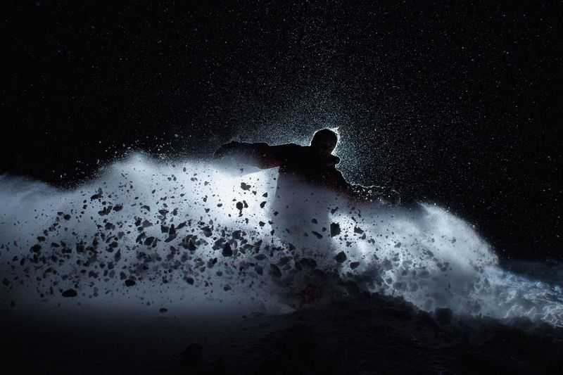 Man Snowboarding At Night