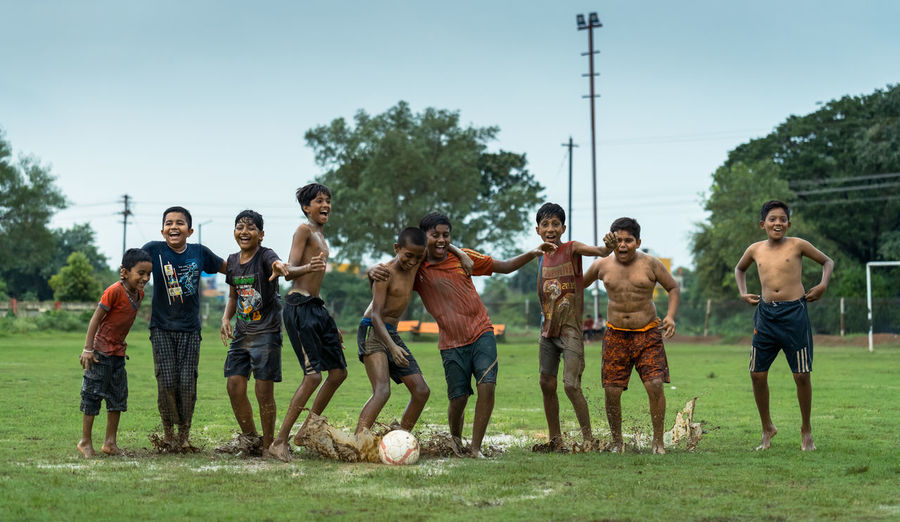 People playing soccer on field against sky