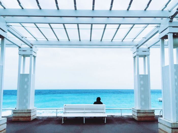 Rear view of man sitting on bench in gazebo against sea