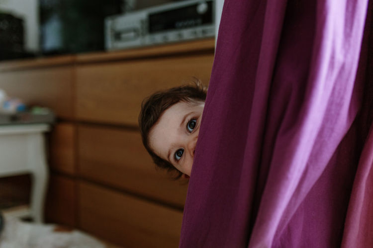 Portrait of cute baby girl peeking from behind curtain