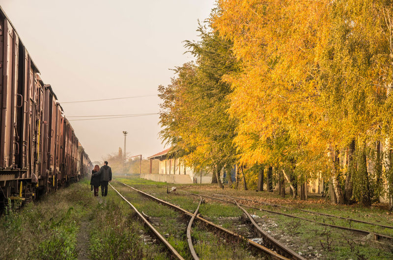 Couple Walking By Train During Autumn