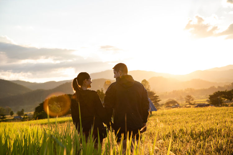 Rear view of couple standing at farm against sky during sunset