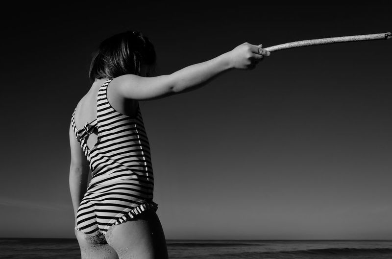 Rear view of girl holding stick at beach