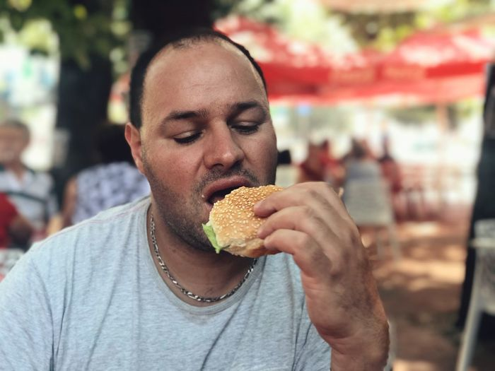 Close-up of mid adult man eating burger at sidewalk cafe