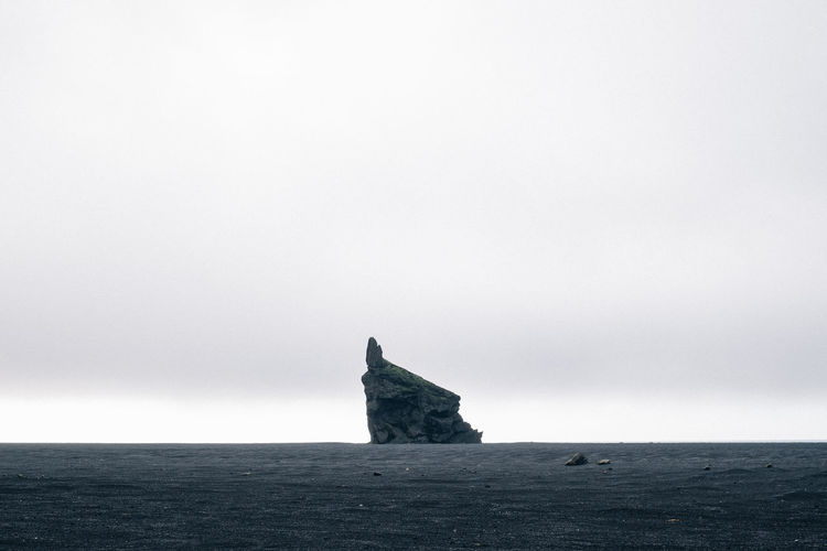 Lone rock at Hjörleifshöfði in South Iceland Sky Sea Tranquil Scene Land Copy Space Tranquility Water Beauty In Nature Horizon Over Water Horizon Scenics - Nature Nature Day No People Rock Non-urban Scene Rock - Object Beach Clear Sky Outdoors Stack Rock Hjörleifshöfði Iceland
