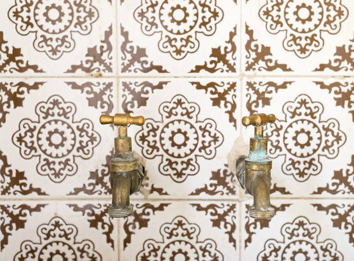 Close-up of faucets on tiled wall