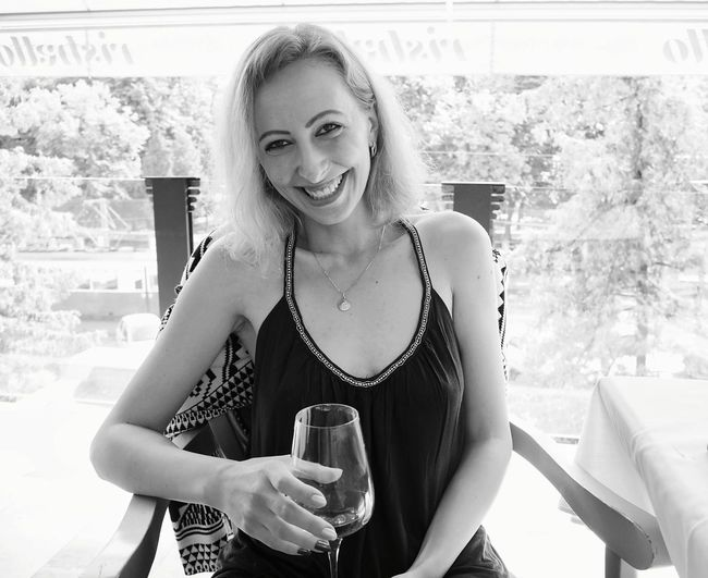 Portrait Of Smiling Young Woman Holding Wineglass While Sitting On Chair At Restaurant